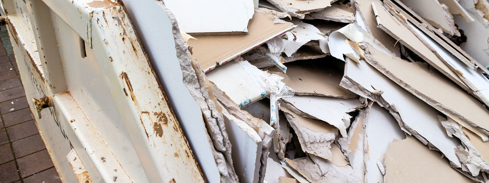in a waste container stacks sheets of plasterboard for their disposal